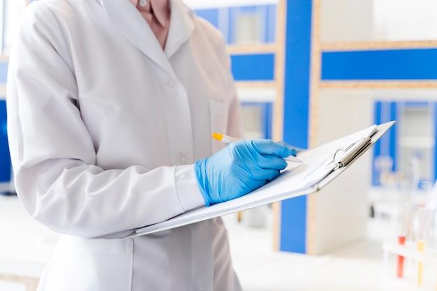 Женский ученый в лаборатории с блокнотом