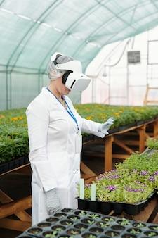 Женщина-ученый в гарнитуре vr держит виртуальный объект, заботясь о зеленых саженцах