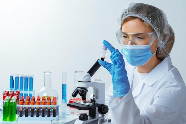 Ученый-женщина смотрит на пробирку с образцом крови в лаборатории
