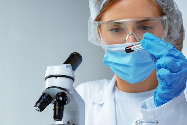 Female scientist looking at test tube with blood sample in laboratory