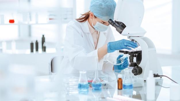 Женщина-ученый смотрит в микроскоп