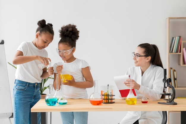 Female scientist observing girls experimenting with chemistry