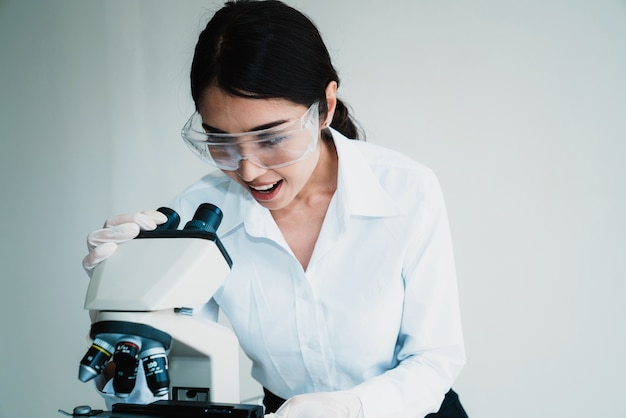 A female scientist in protective glasses works with a microscope