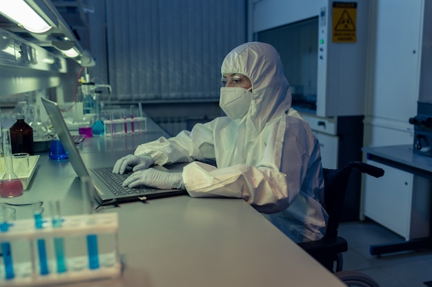 Female scientist in protective workwear sitting at the table and typing on laptop  during her work in the lab