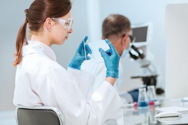 Женщина-ученый надевает защитную маску в лаборатории.