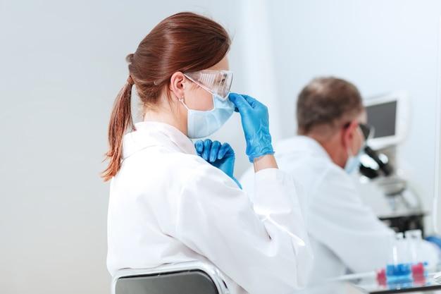 Женщина-ученый сидит за лабораторным столом