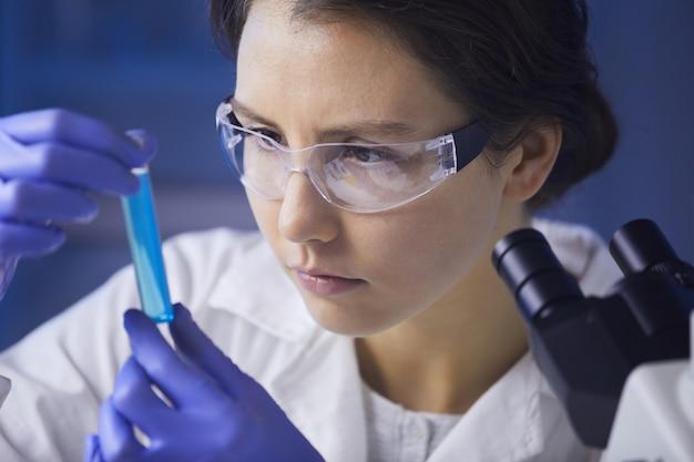 Female scientist studying test sample