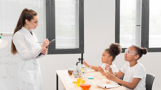 Female scientist teaching girls about chemistry