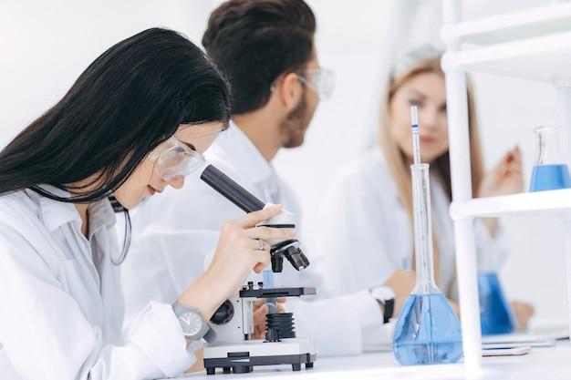 女性の科学者は実験室で顕微鏡を使用しています。科学と健康