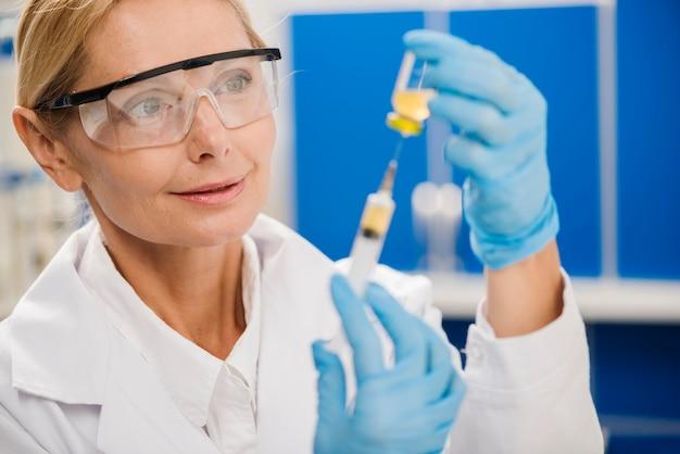 Female scientist using a syringe