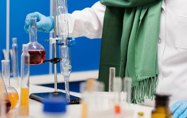 Женщина-ученый с хиджабом в лаборатории с веществом