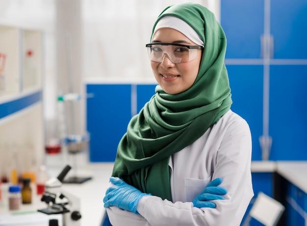 Женщина-ученый с хиджабом позирует в лаборатории