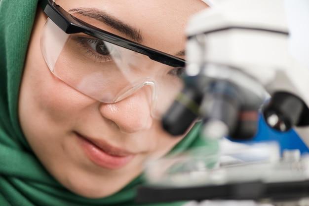 Женщина ученый с хиджабом работает в лаборатории