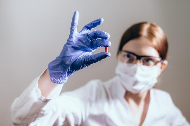 保護マスクを付けた女性科学者が薬の丸薬を見せています。斬新で革新的な治療コンセプト。健康の概念