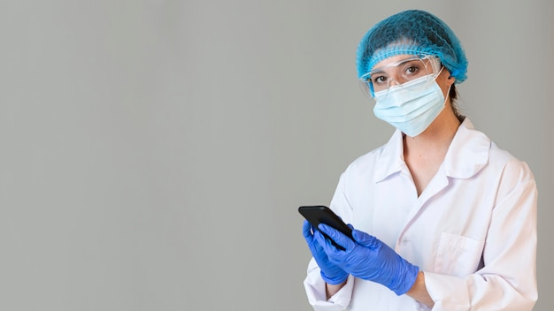 安全メガネとスマートフォンを保持している医療マスクを持つ女性科学者