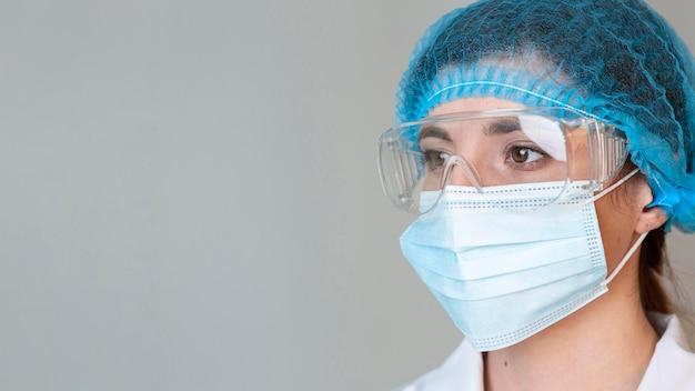 Scienziato femminile con occhiali di sicurezza, retina per capelli e mascherina medica