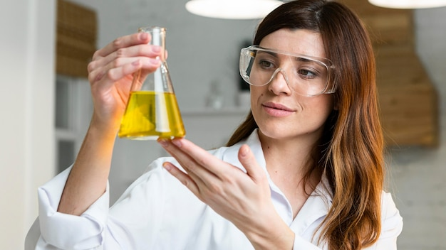 Female scientist with safety glasses holding test tube