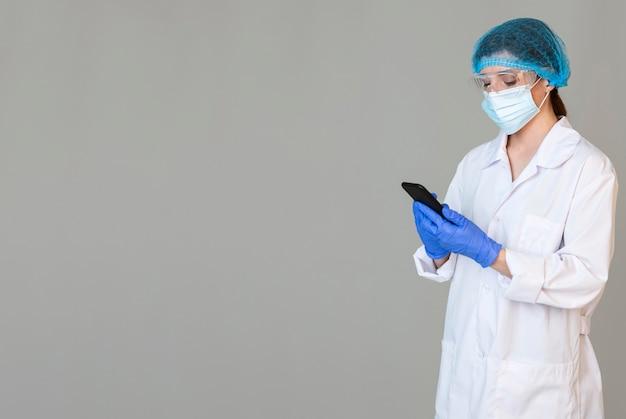 Scienziato femminile con occhiali di sicurezza e mascherina medica che tiene smartphone con lo spazio della copia