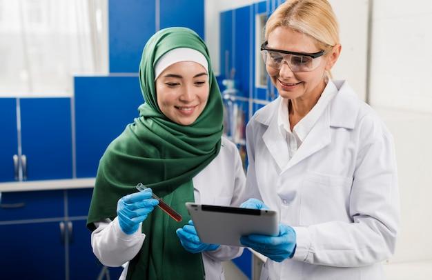 Женщины-ученые в лаборатории работают с планшетом