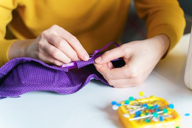 Женщина-швея шьет корсет иглой во время работы на своем рабочем месте