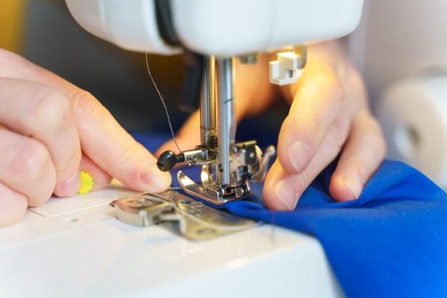Женщина-швея шьет или сшивает ткань на профессиональной машине
