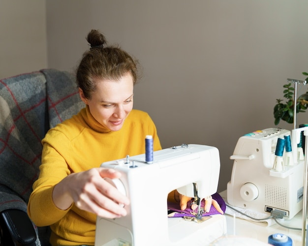 Female seamstress using sewing machine while working at home