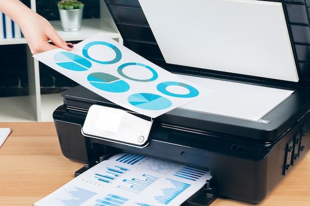 Female secretary making photocopies on xerox machine in office