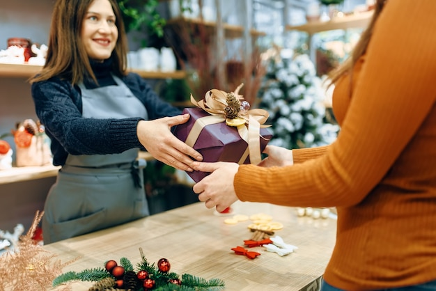 Женщина-продавец дарит покупателю рождественскую подарочную коробку в упаковке ручной работы.