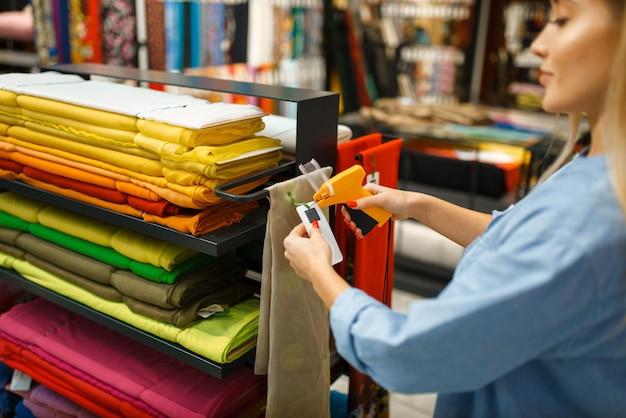 Женский продавец держит ткань в текстильном магазине. полка с тканью для шитья
