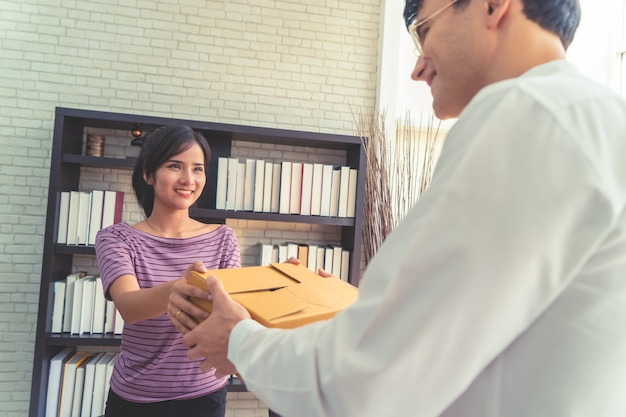 Female seller home business owner handling package to customer