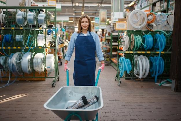 エプロンの女性売り手は庭師のための店で庭のカートを保持します。女性は花卉園芸のために店で機器を販売します、花屋