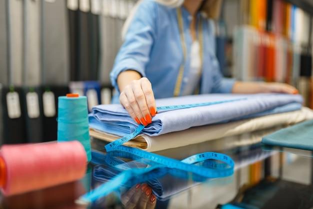 Женщина-продавец измеряет ткань в текстильном магазине. полка с тканью для шитья