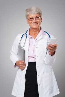 Medico senior femminile utilizzando dalla tecnologia digitale