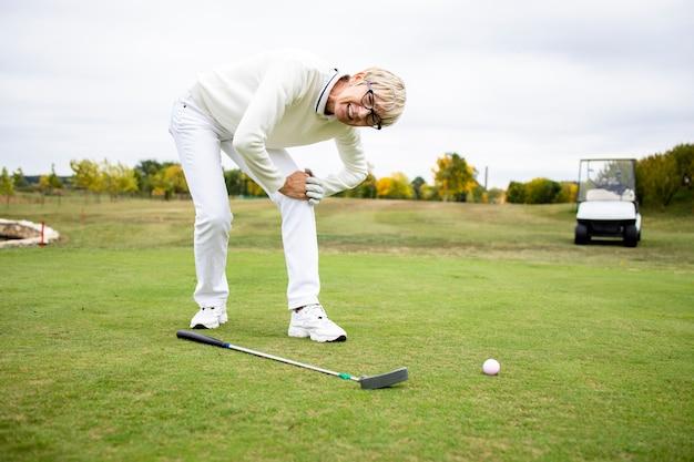 ゴルフトレーニングで健康上の問題と膝の痛みを抱えている女性シニアゴルファー。