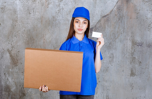 Female service agent in blue uniform holding a cardboard box and presenting her business card