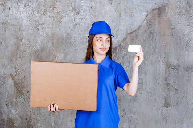 Female service agent in blue uniform holding a cardboard box and presenting her business card.