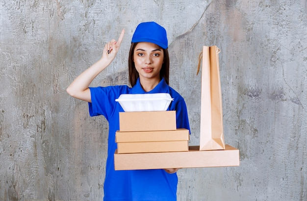 Female service agent in blue uniform holding cardboard boxes, shopping bax and takeaway boxes while looking confused and dreaming.
