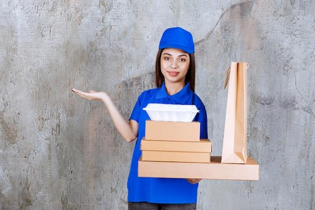 Agente di servizio femminile in uniforme blu con scatole di cartone, carrello della spesa e scatole da asporto