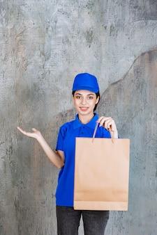 Agente di servizio femminile in uniforme blu che tiene un sacchetto della spesa del cartone.