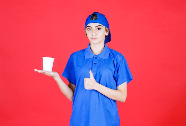 Female service agent in blue uniform holding a disposable cup of drink and enjoying the taste.
