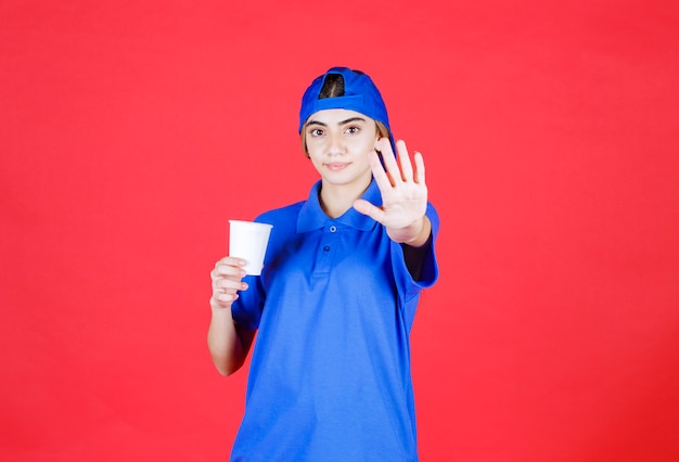 Female service agent in blue uniform holding a disposable cup of drink and stopping someone.