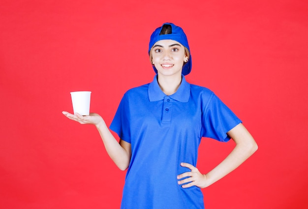 Female service agent in blue uniform holding a disposable cup of drink .