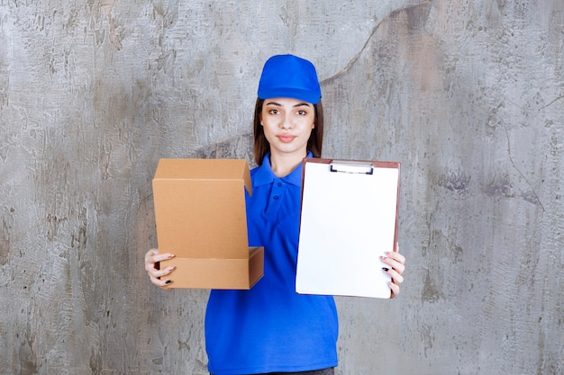 Female service agent in blue uniform holding an open cardboard box and presenting the signature list.