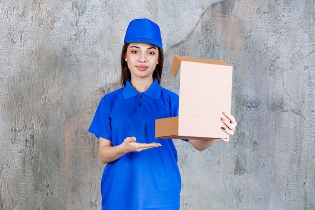 Female service agent in blue uniform holding an open cardboard box .