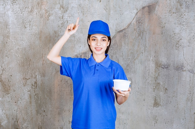 Female service agent in blue uniform holding a plastic bowl and looks confused and thoughtful or having a good idea.