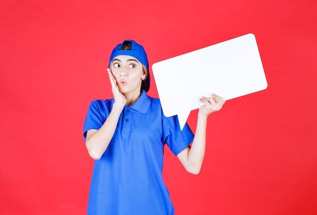 Agente di servizio femminile in uniforme blu che tiene un banco informazioni rettangolo e sembra confuso o elettrizzato.