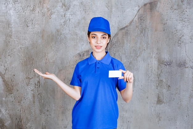 Female service agent in blue uniform presenting her business card and pointing at her colleague.