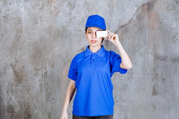 Agente di servizio femminile in uniforme blu che presenta il suo biglietto da visita.