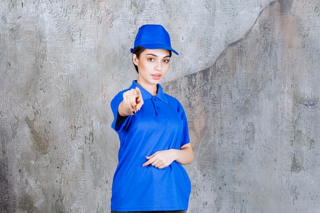 Female service agent in blue uniform showing the person ahead.