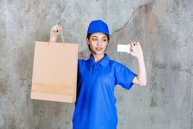 段ボールの買い物袋を持って名刺を提示する青い制服を着た女性サービスエージェント。